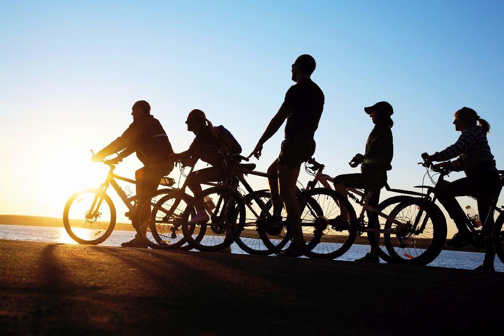 Silhouette einer Gruppe mit E-Bikes vor einem Sonnenuntergang