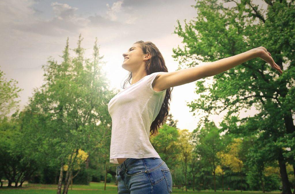 Junge Frau genießt die Natur, streckt die Arme und atmet tief durch. Heuschnupfen entgegenwirken.