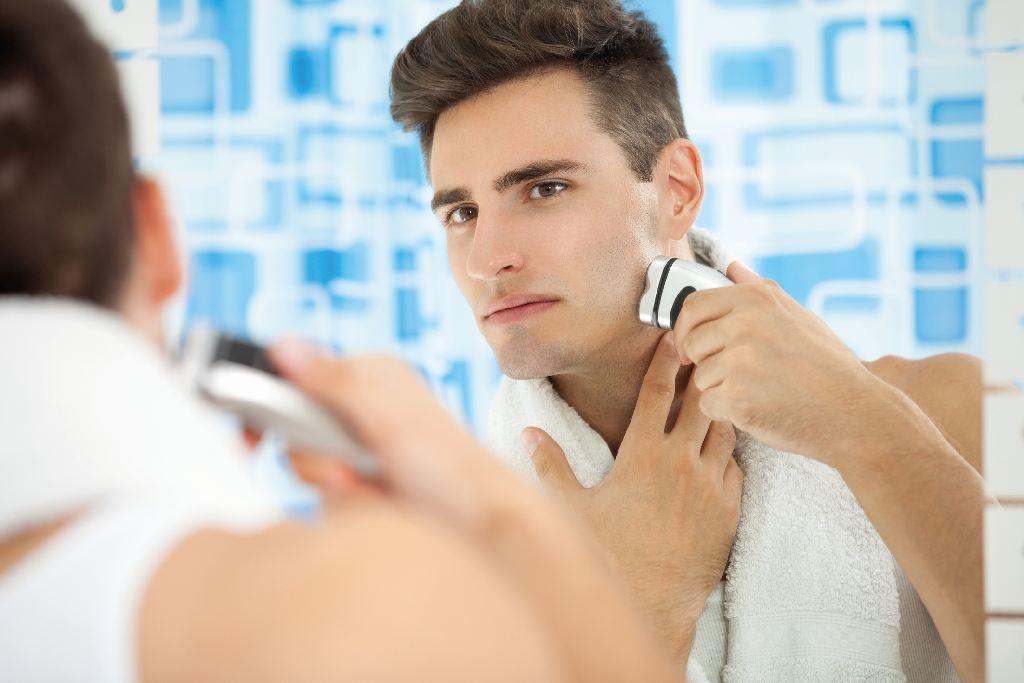 Junger Mann rasiert sich vor dem Spiegel (Haut)