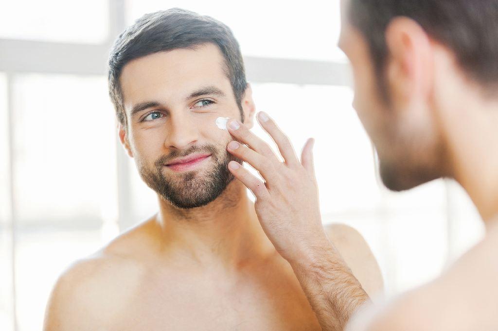 Pflege für Männerhaut: Ein Mann mit Bart und nacktem Oberkörper benutzt Gesichtscreme.