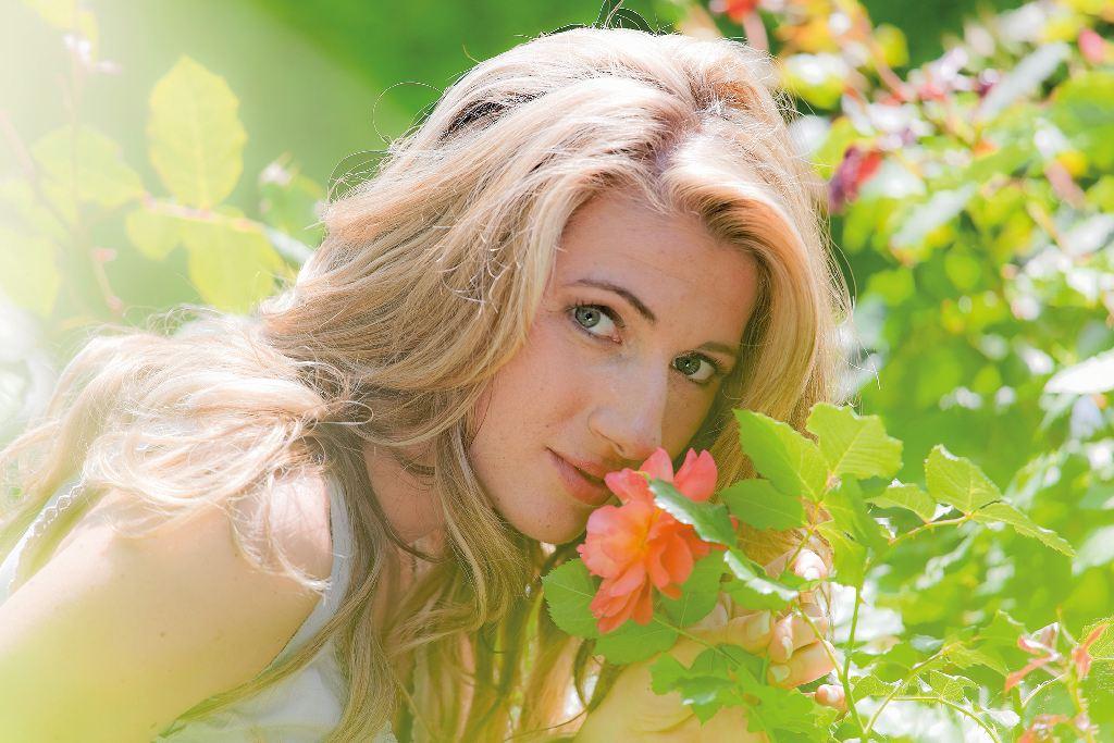 Frau riecht an einer Rose im Garten. Erholung und relaxen, um gesund zu leben
