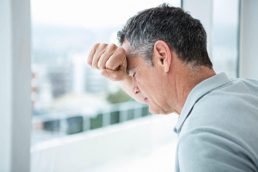 Man lehnt gegen eine Fensterscheibe (Stressursachen auf den Grund gehen)