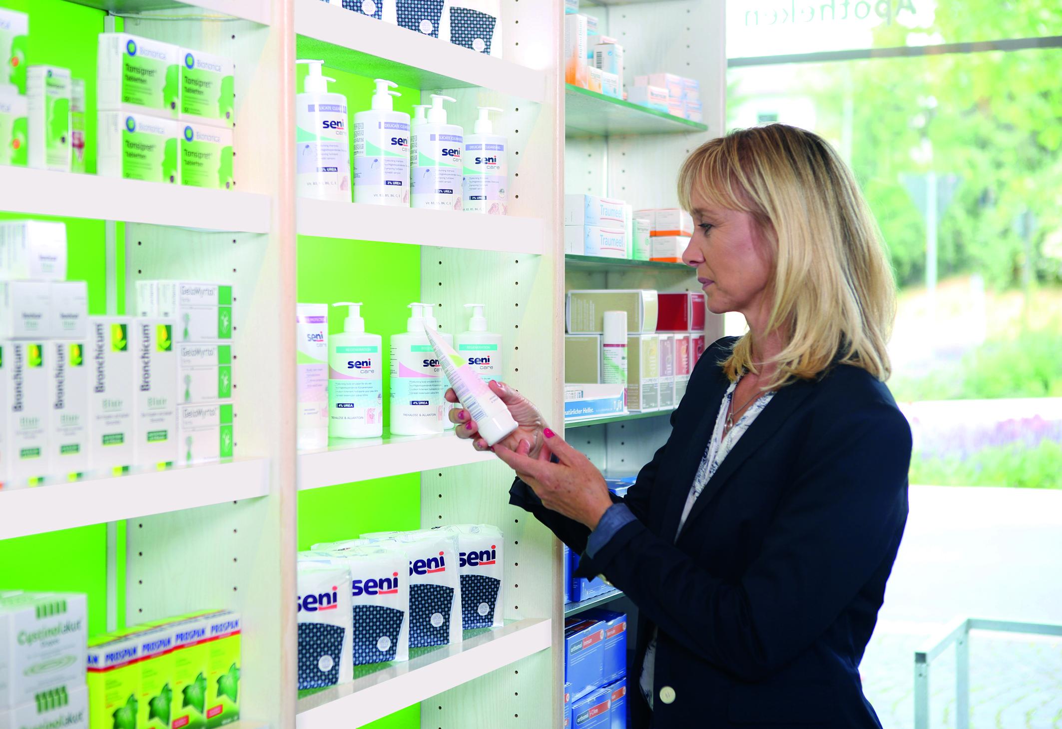 Eine Frau steht vor einem Regal und schaut sich Pflegeprodukte für trockene Haut an.