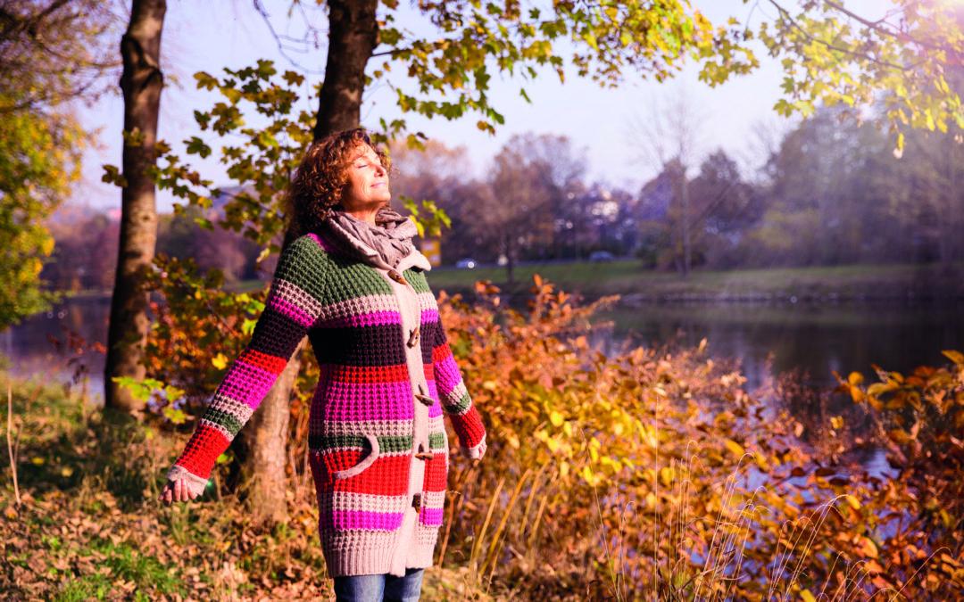 "Frau ""tankt"" Vitamin D am See in der Herbstsonne."