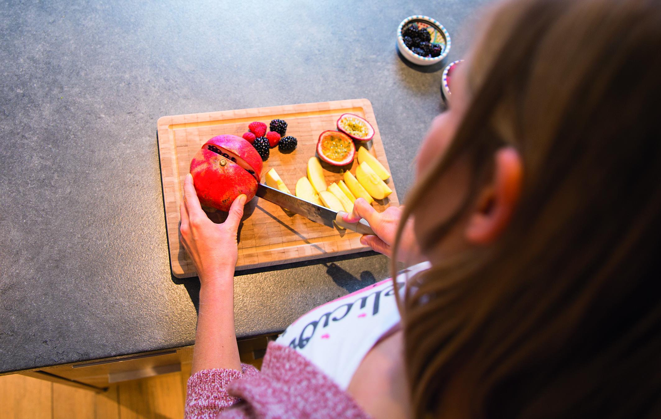 Eine Frau schneidet Obst auf einem Brett, um der Frühjahrsmüdigkeit entgegenzuwirken