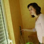 Frau verdunkelt Fenster mit Rollläden. (gesunder Schlaf)