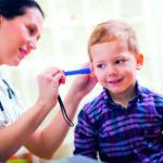 Eine Ärztin leuchtet in das Ohr eines Jungen und prüft dessen Ohrhygiene