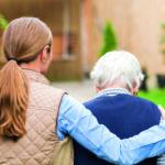 Frau führt demenzkranke ältere Frau.