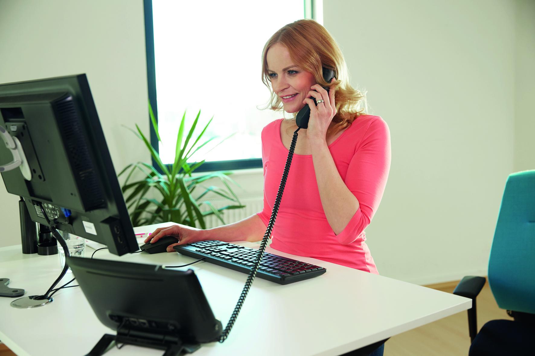 Frau im pinken T-Shirt sitzt vor dem PC und telefoniert. (Was bei Verspannungen hilft)