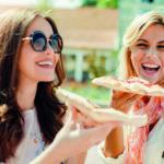 Zwei lachende junge Frauen essen Pizza – abnehmen mit Genuss.