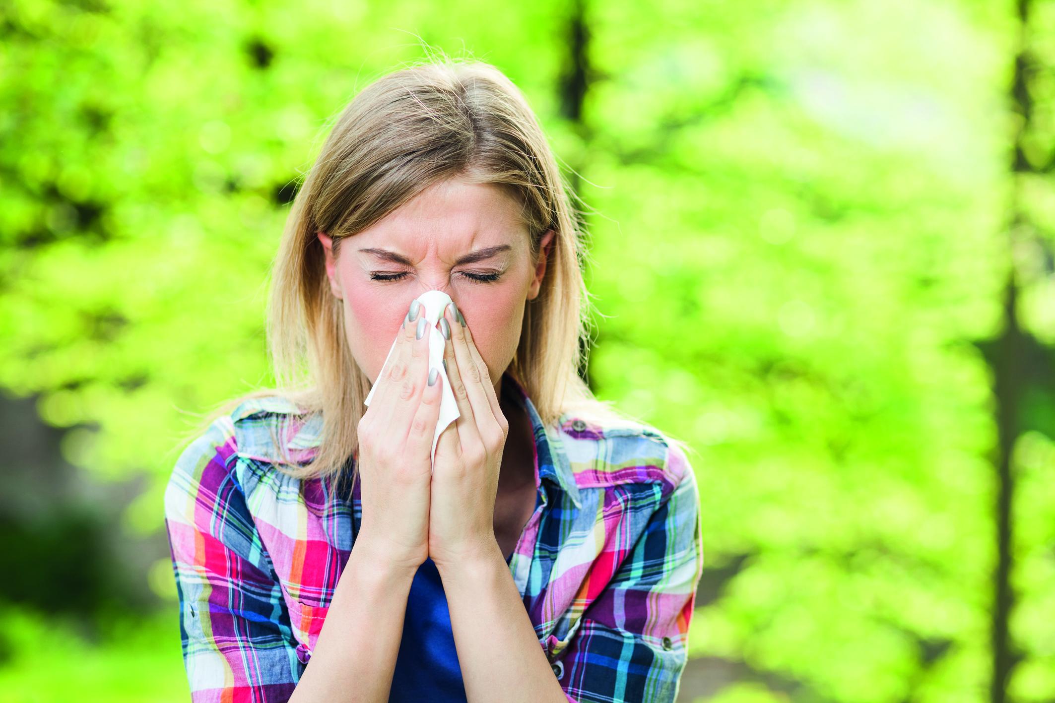 Junge Frau putzt sich die Nase wegen einer Pollenallergie. Im Hintergrund grüne Laubbäume.