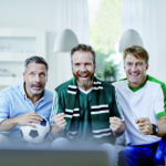 Drei Männer mittleren Alters mit Fußball auf dem Sofa. (Prostata)