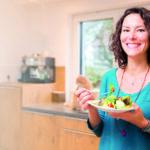 Frau in der Küche isst gesundes Gemüse und lächelt in die Kamera (Die Schilddrüse)