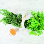 Kräuter in einem Tragekorb und ein Glas Orangensaft (Säure-Basen-Haushalt)