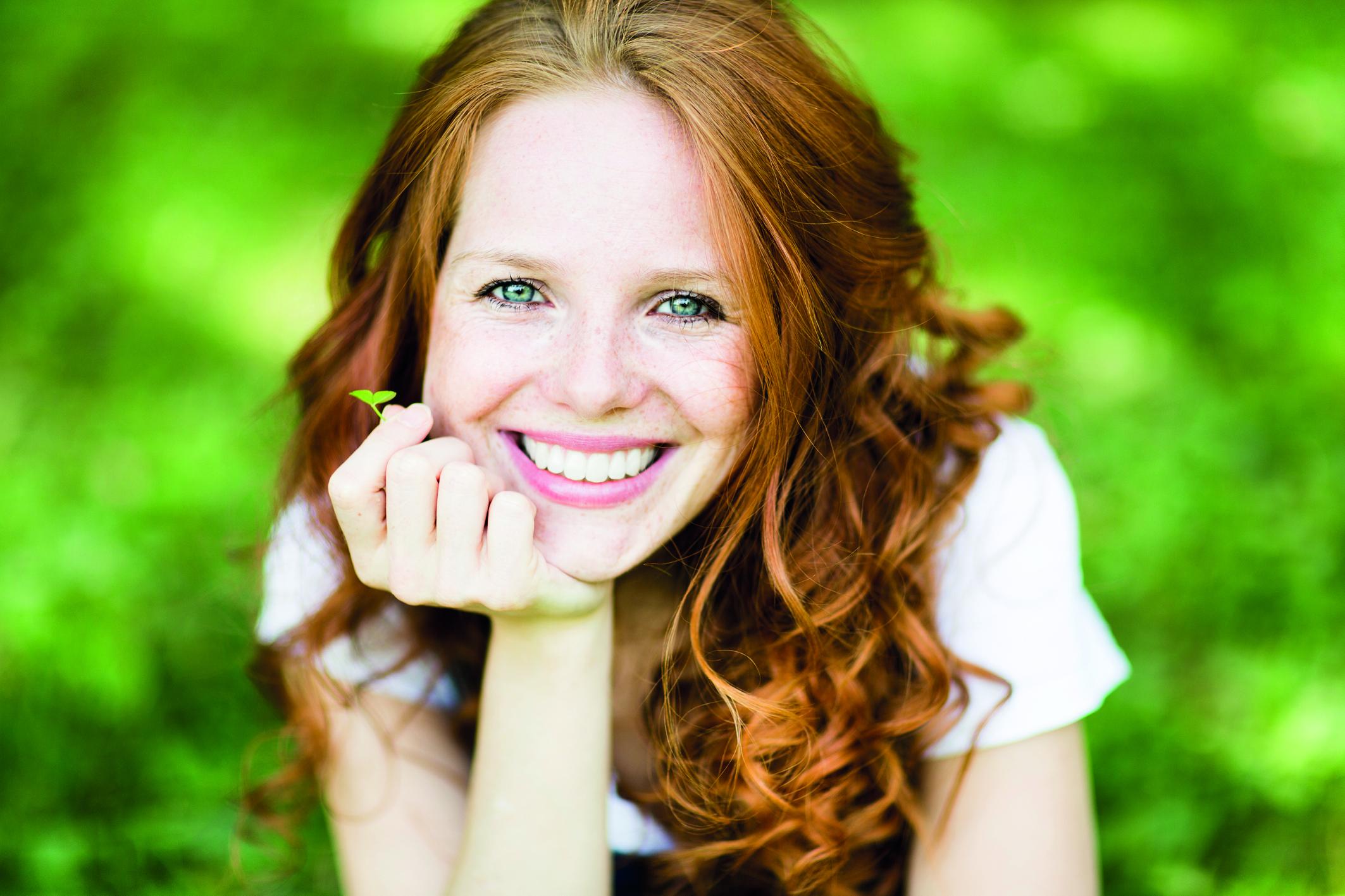 Rothaarige Frau mit strahlendem Lächeln vor grünem Hintergrund. (Erste Hilfe für Zähne)