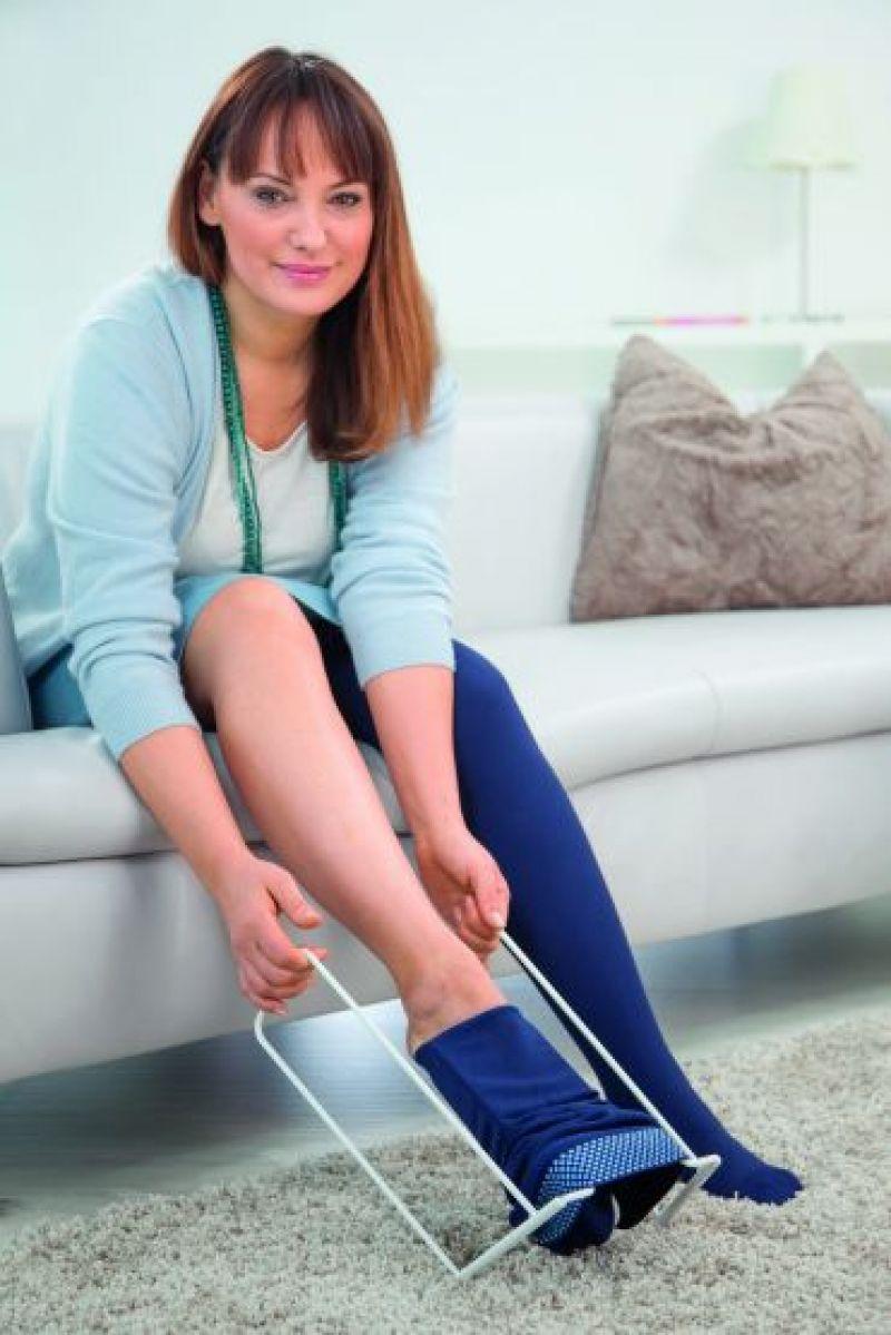 Eine Frau zieht sich mithilfe eines Hilfgerätes Kompressionsstrümpfe an