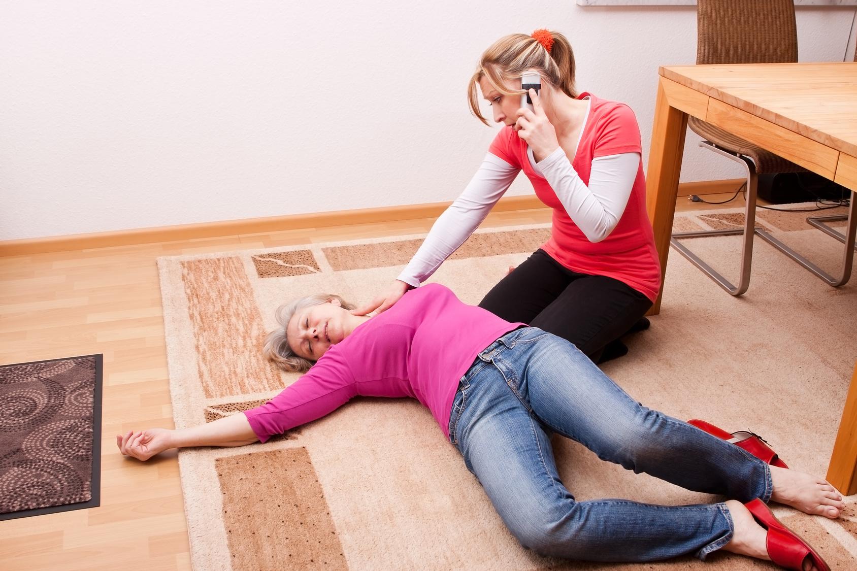 Eine Seniorin ist bewusstlos und liegt auf dem Boden. Eine Frau kniet neben ihr und alarmiert den Rettungsdienst über die Notrufnummer 112. (ärztliche VErsorgung)