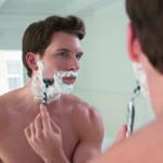 Tägliche Pflege: Ein Mann steht vor dem Spiegel und rasiert sein Gesicht