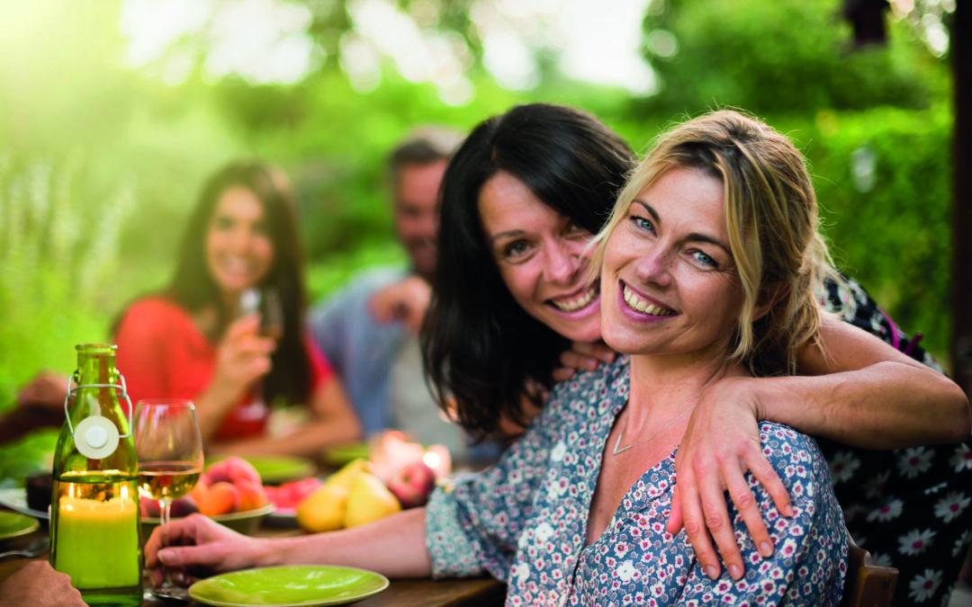 Angenehm Abnehmen: Zwei Frauen liegen sich in den Armen, sitzen an einem gedeckten Tisch und lächeln in die Kamera
