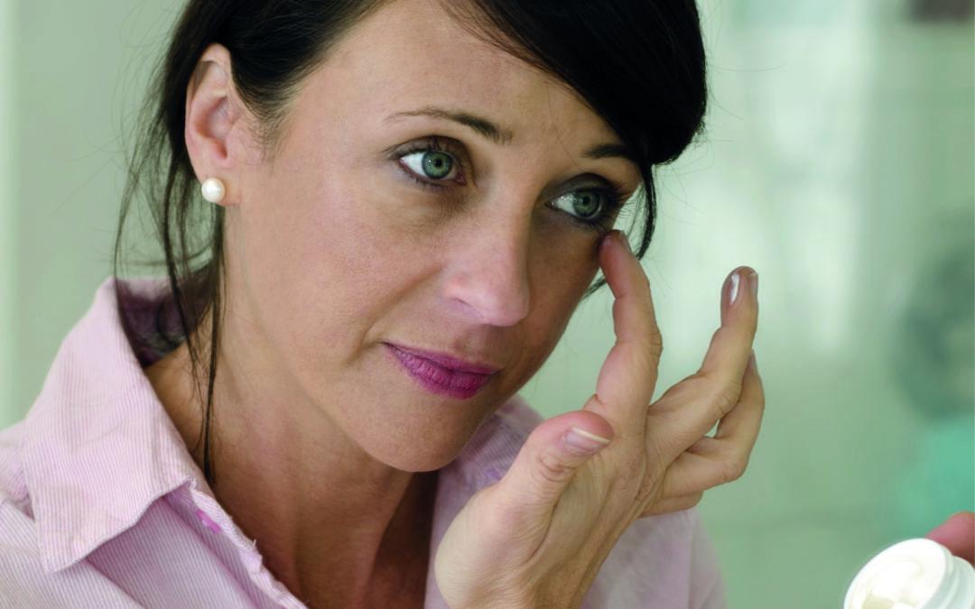 Eine Frau cremt sich mit einem schwefelhaltigen Produkt ein, um ihre unreine Haut zu verbessern