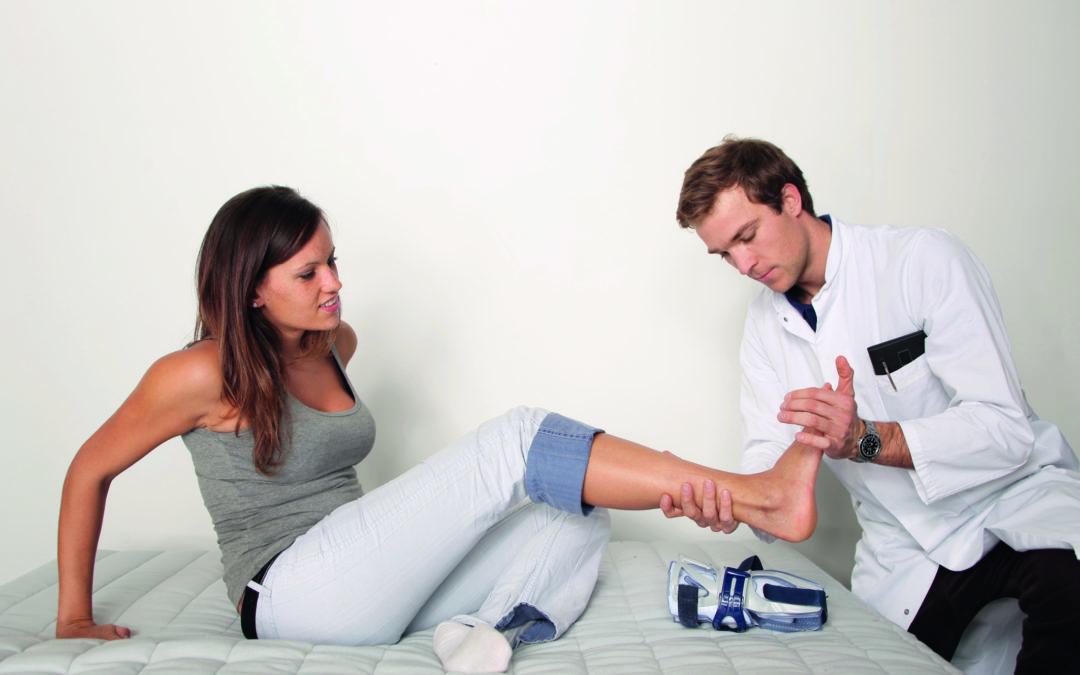 Eine Frau ist nach einem Arbeitsunfall zu einem Spezialisten gegangen und lässt sich ihren Fuß untersuchen (Arbeitsunfälle)