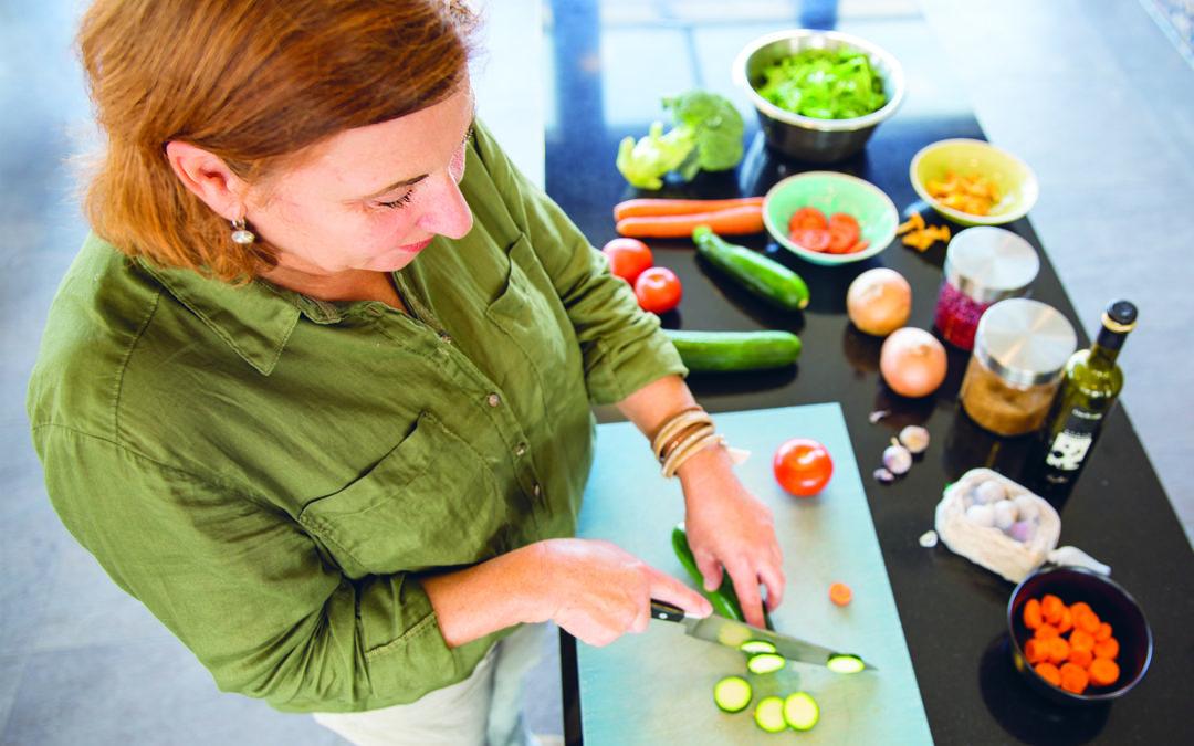 Natürlich durch die Wechseljahre: Eine Frau schneidet Gemüse klein