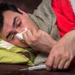 Ein Mann mit Erkältung hält ein Taschentuch und ein Thermometer. (ärztliche Versorgung)