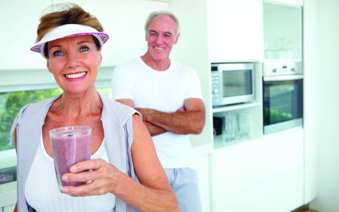 Ein älteres Paar steht in der Küche. Sie hält einen Smoothie in der Hand.