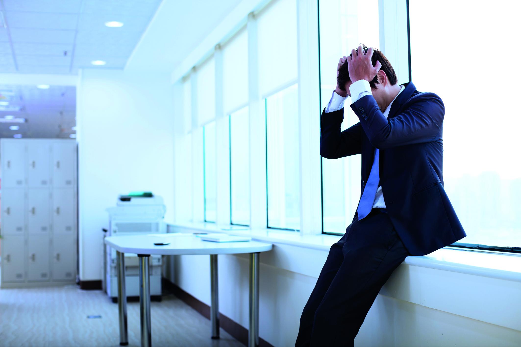 Schwitzen bei Stress: Ein Mann im Anzug schlägt die Hände über dem Kopf zusammen und ist gestresst