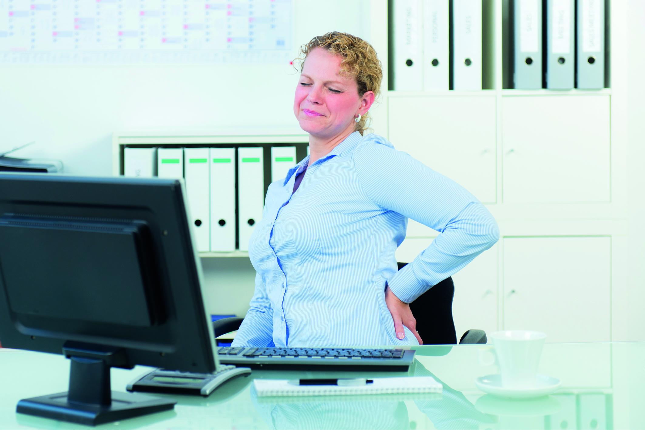 Rückenschmerzen: eine Frau sitzt an ihrem Schreibtisch und hält sich vor Schmerzen den Rücken