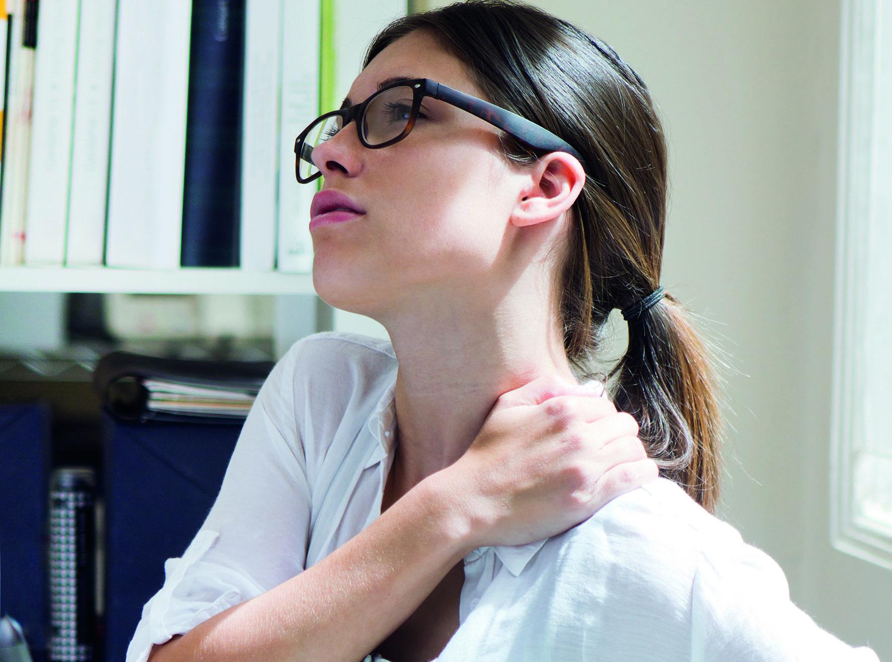 Stress verursacht Beschwerden: eine Frau fasst sich aufgrund von Schmerzen und Verspannung an ihren Nacken.