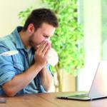 Ein Mann sitzt am Schreibtisch vor seinem Laptop und putzt sich seine Nase. Er geht trotz Krankheit ins Büro