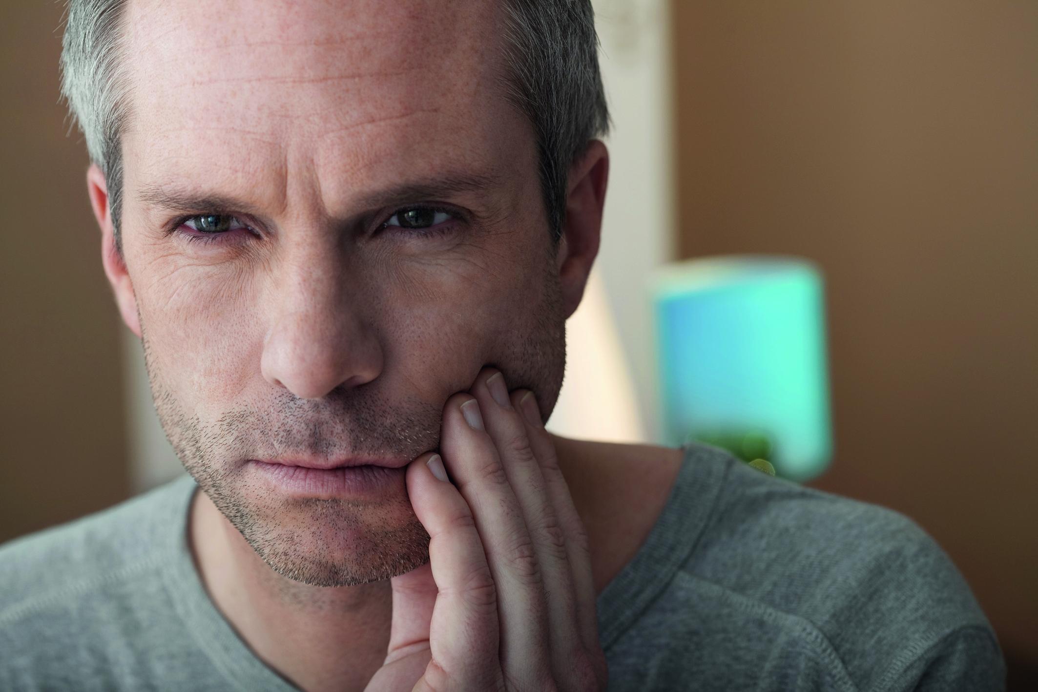 Ein Mann hat Probleme mit den Zähnen und hält sich vor Schmerzen die linke Wange