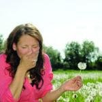 Eine Frau steht in der Natur und niest: Sie leidet an Heuschnupfen
