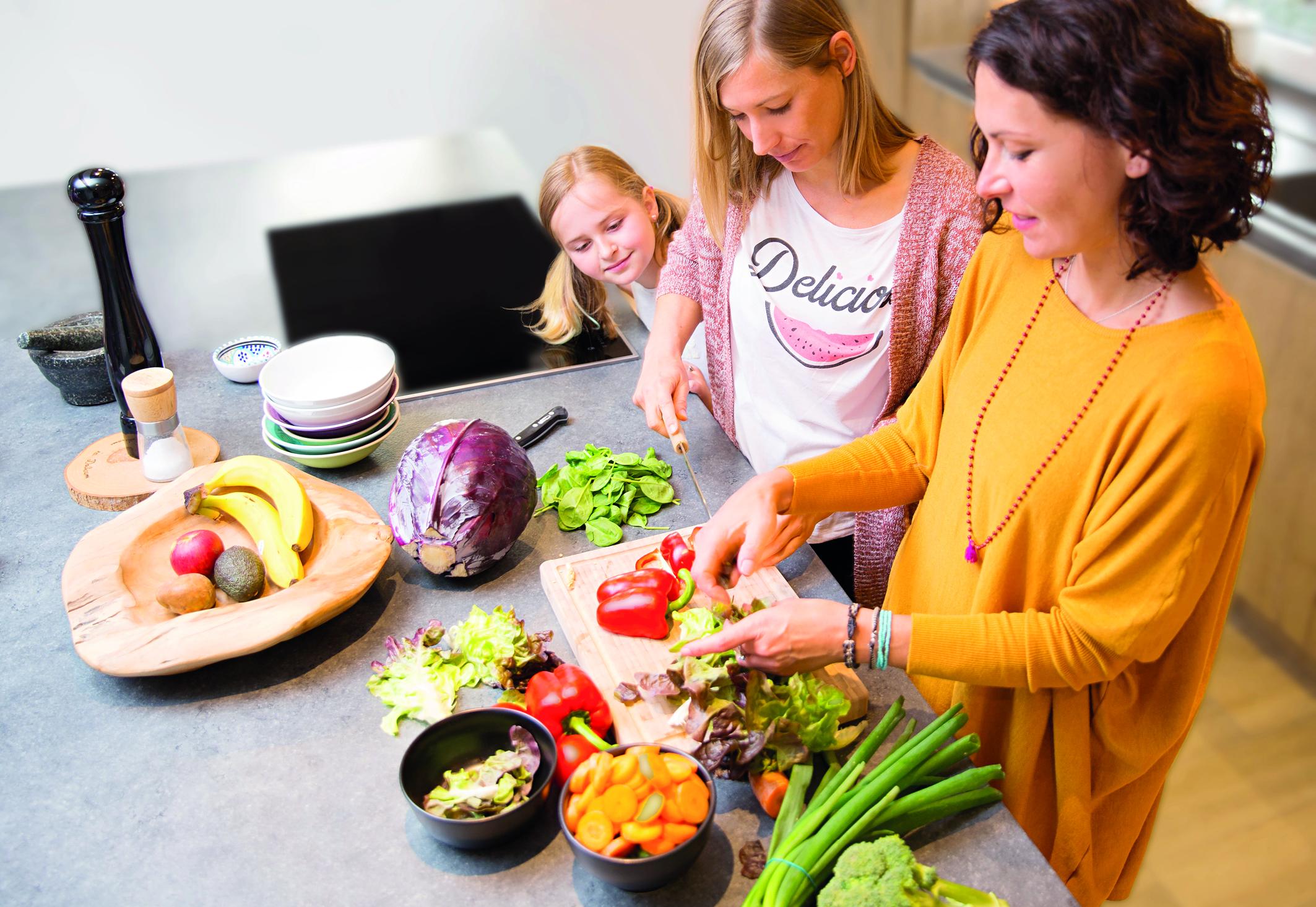 Zwei Frauen schneiden Gemüse klein, um dies später dann fermentieren zu können