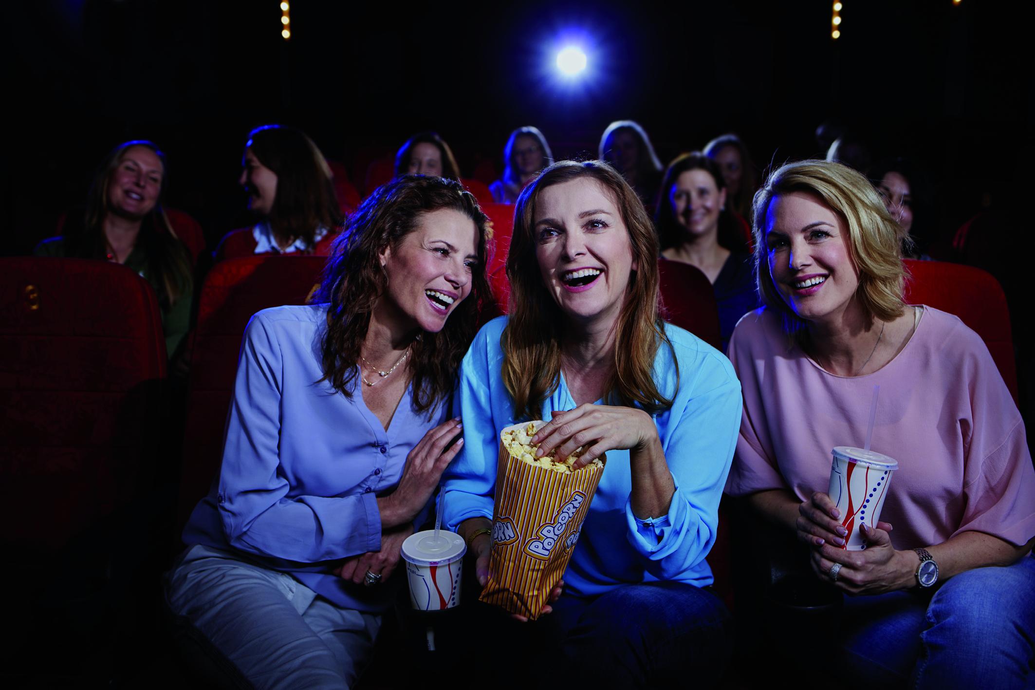 Drei Frauen genießen einen Kinobesuch, trotz Blasenschwäche