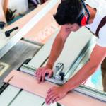 Verletzungsrisiken bei der Arbeit: Ein Mitarbeiter im Handwerk arbeitet an einer Maschine