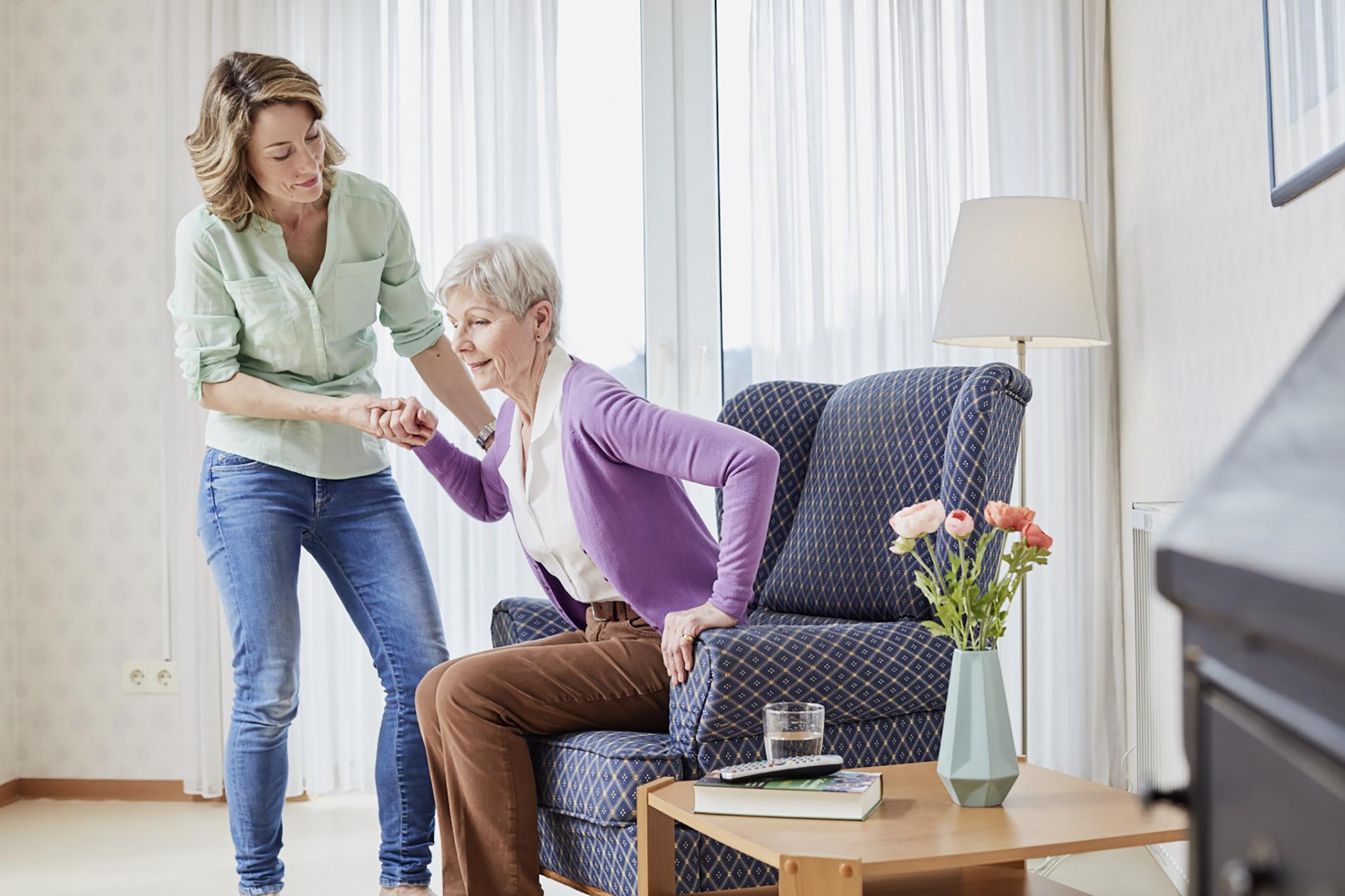 Pflegebedürftigkeit: Eine Frau hilft einer älteren Dame aufzustehen