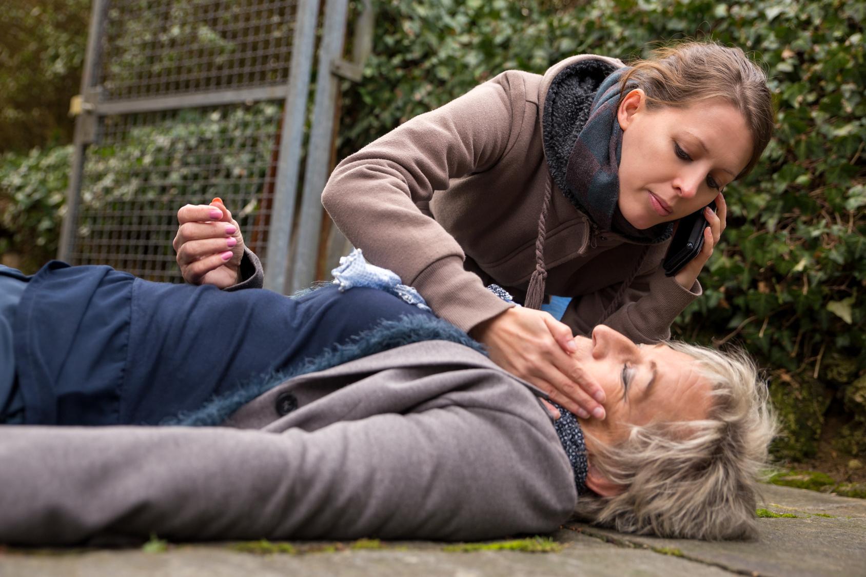Eine ältere dame liegt bewusstlos am Boden, ein Mädchen beugt sich mit besorgtem Gesichtsausdruck über sie.