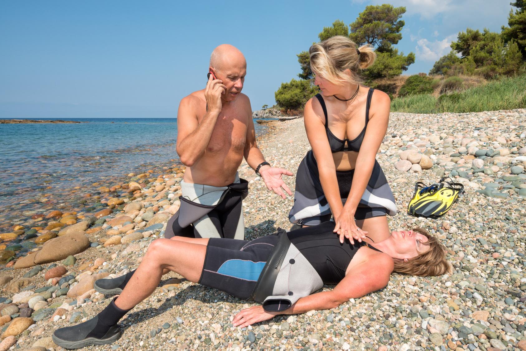 Eine Frau im Neoprenanzug wird am Strand reanimiert. Daneben kniet ein Mann und alarmiert die Rettungskräfte.