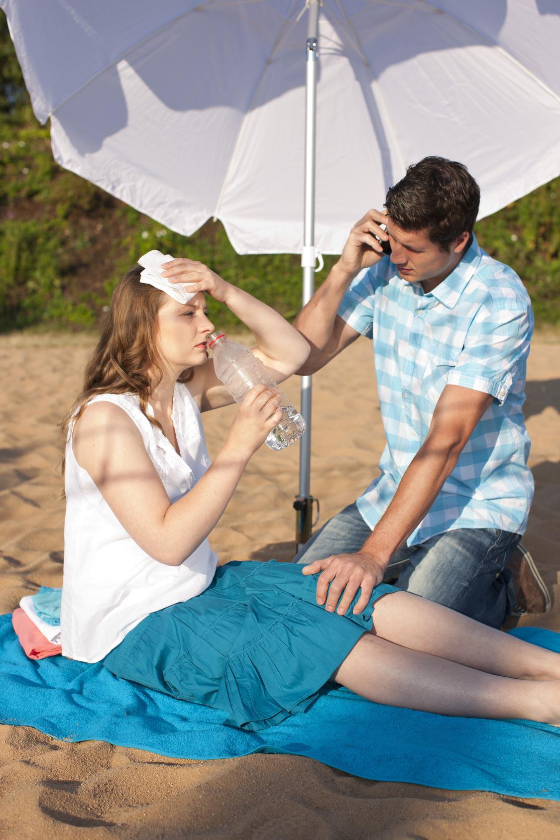 eine sehr blasse Frau sitzt am Strand kühlt sich die Stirn sie wird von einem Mann betreut, der ein Handy in der Hand hält. (Sonnenbrand)