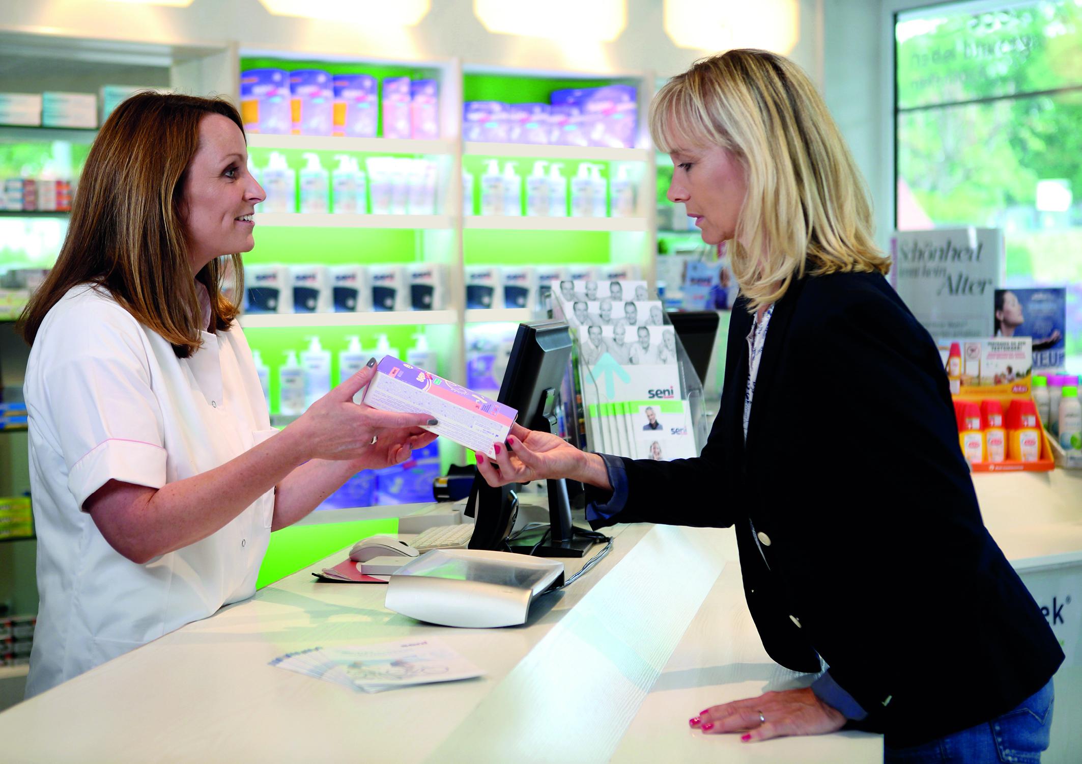 Eine Frau besorgt sich in der Apotheke ein Medikament gegen Blasenentzündung