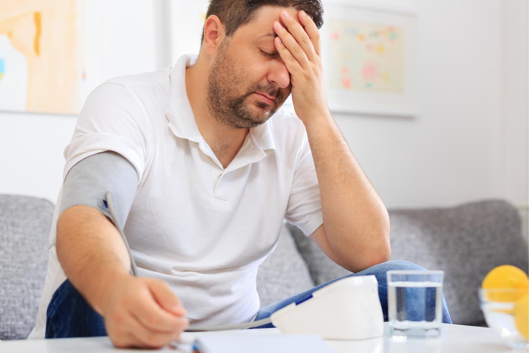Ein erschöpfter Mann misst seinen Blutdruck und hält sich dabei den Kopf. (Hypertension)