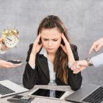 Eine Frau sitzt an einem Schreibtisch vor diversen Büroutensilien, während ihr ein klingelndes Handy, ein Wecker und eine Uhr hingehalten werden. (Stress)
