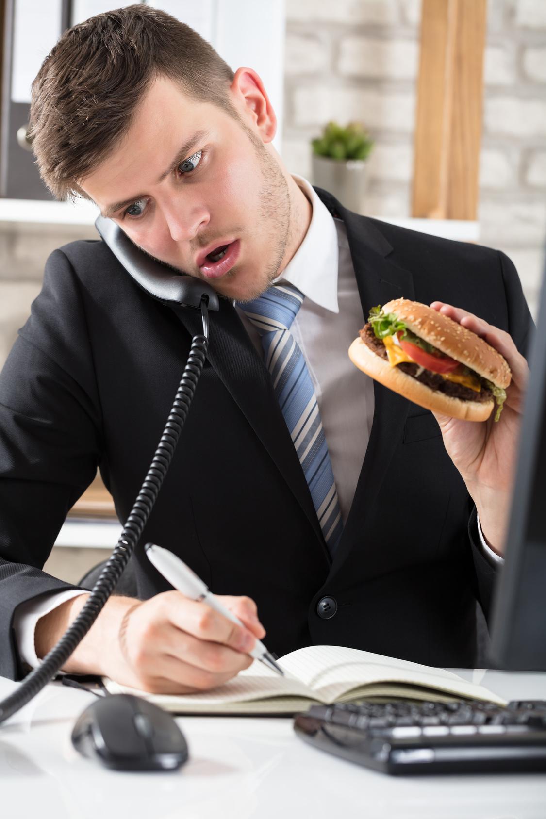 ein Mitarbeiter im Büro telefoniert, macht Notizen und isst zeitgleich einen Burger.