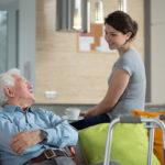 Senior spricht mit Pflegerin (Pflegebedürftigkeit)