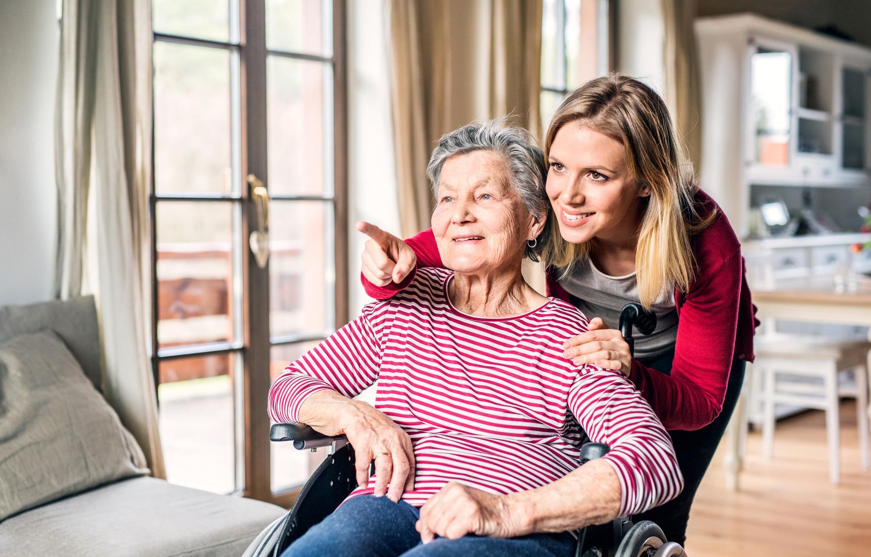 Eine Seniorin im Rollstuhl wird von einer jungen Frau betreut. (Betreutes Wohnen)