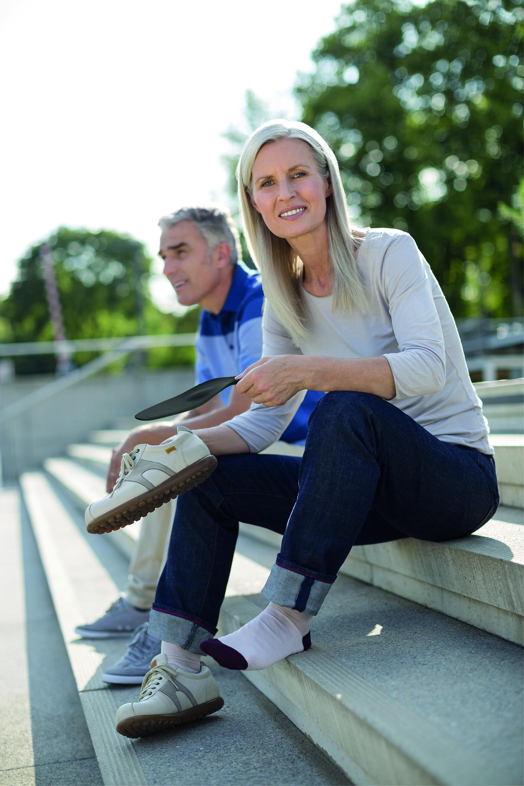 Eine Frau zieht sich ihre Schuhe, mit spezieller Schuheinlage an. Diese lindern die Schmerzen, der Arthrose des Großzehengrundgelenks.