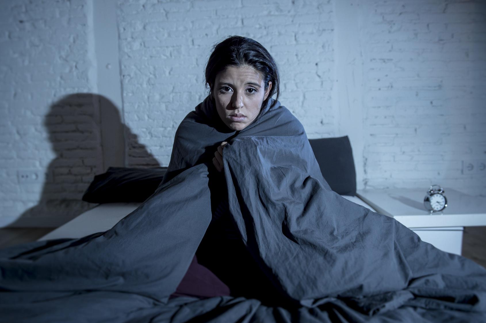 Eine junge Frau sitzt, in Decken eingewickelt, auf dem Bett und macht ein unglückliches Gesicht. (Winterdepression)