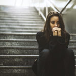 eine depressive Frau sitzt im Schatten auf einer dunklen Steintreppe.